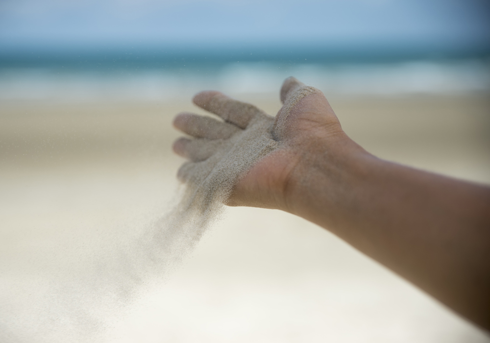 Hand letting go of sand freedom concept