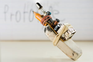 "Various items including copper wire, batteries, a spring, pencil, and eraser tied together to form a device in front of a background with the word ""Prototype."""