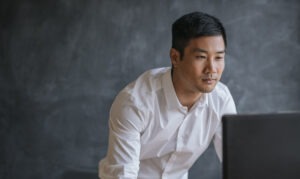 Focused Asian businessman leaning over his desk in front of a blank chalkboard working on a computer
